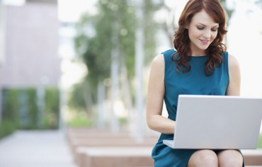 Businesswoman working on laptop --- Image by © Laura Doss/Corbis