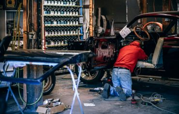 A suspicious man repairing a car