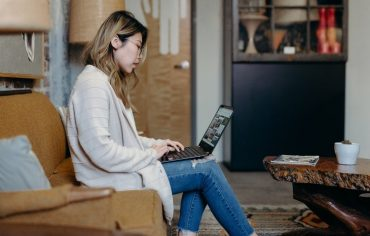 how-much-mortgage-can-i-afford-woman-on-couch-laptop