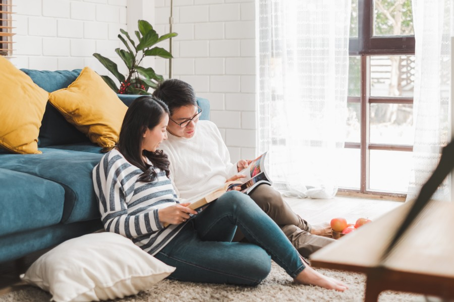 reduced-income-budgeting-couple-reading-on-ground-by-couch
