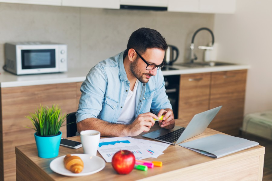 is-now-a-good-time-to-invest-man-laptop-kitchen-croissant-apple-plant