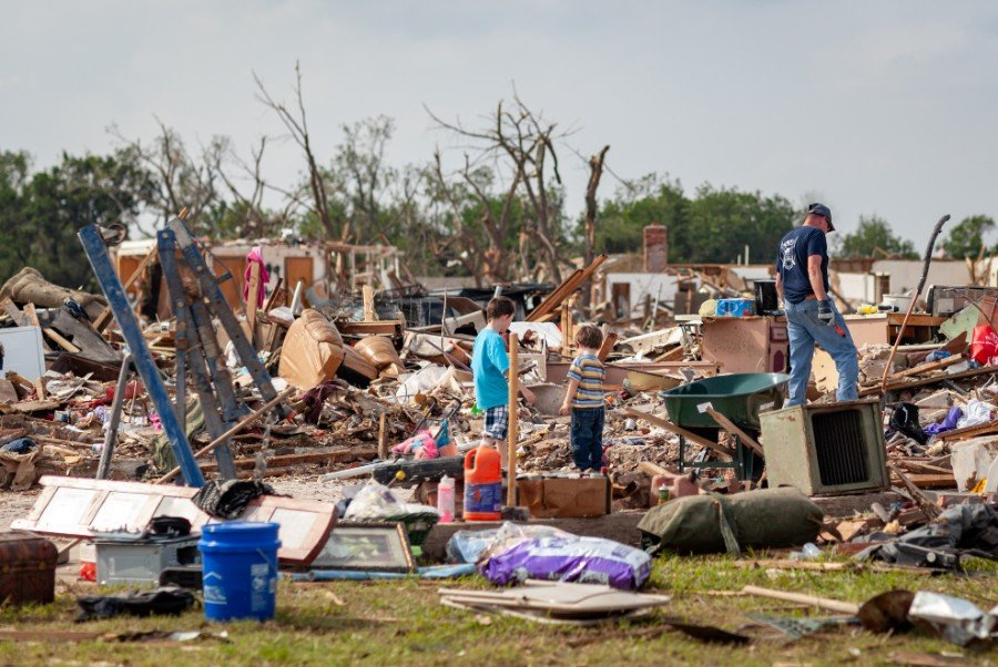 hurricane-house-insurance-family-stands-amid-rubble