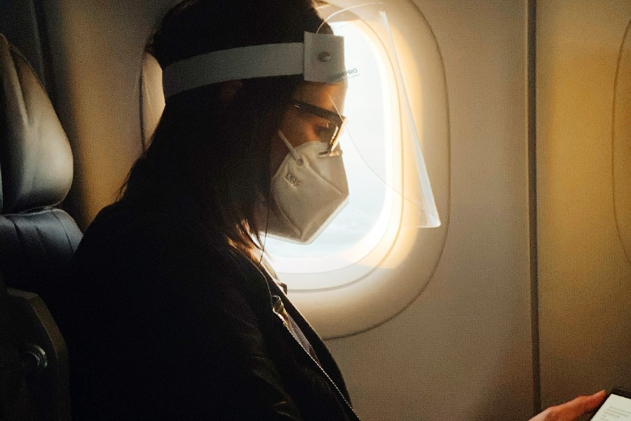 travel-insurance-during-covid-masked-woman-on-plane-reading