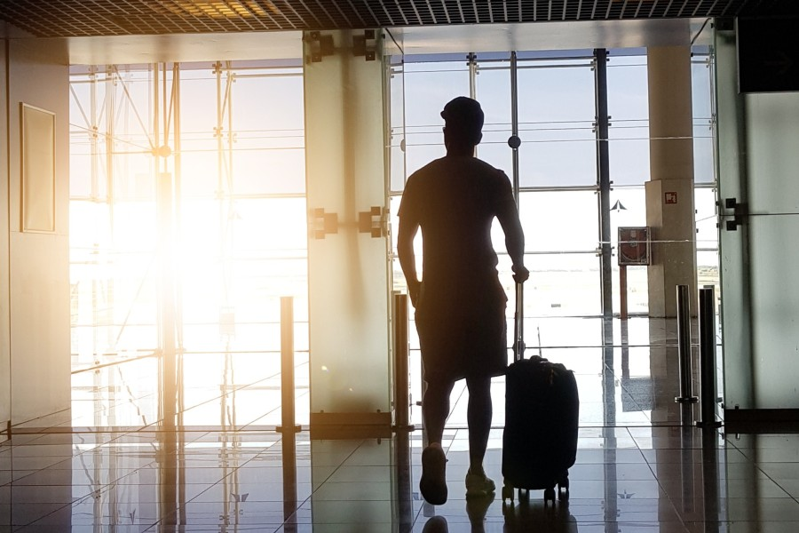travel-points-credit-card-covid-man-walking-in-airport-luggage