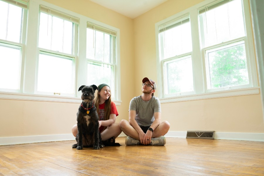 how to make an offer on a house in canada couple sits in empty house with dog