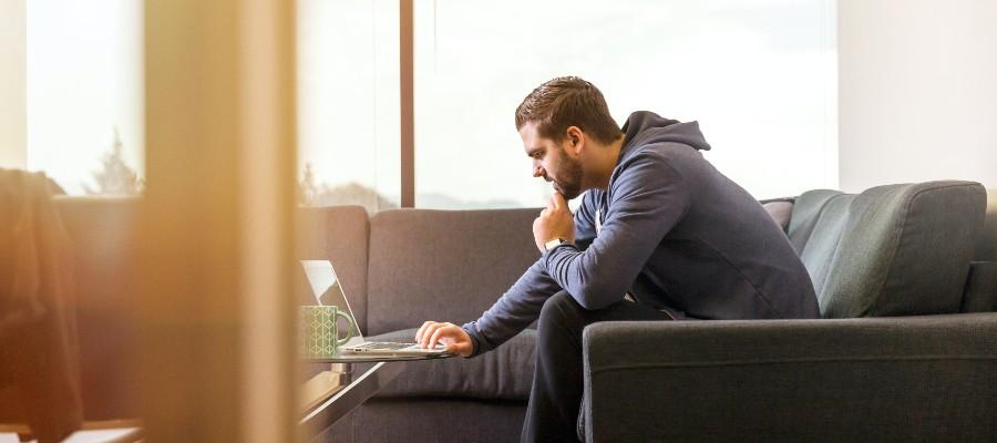 negative-balance-credit-card-man-sitting-concern-researching-laptop