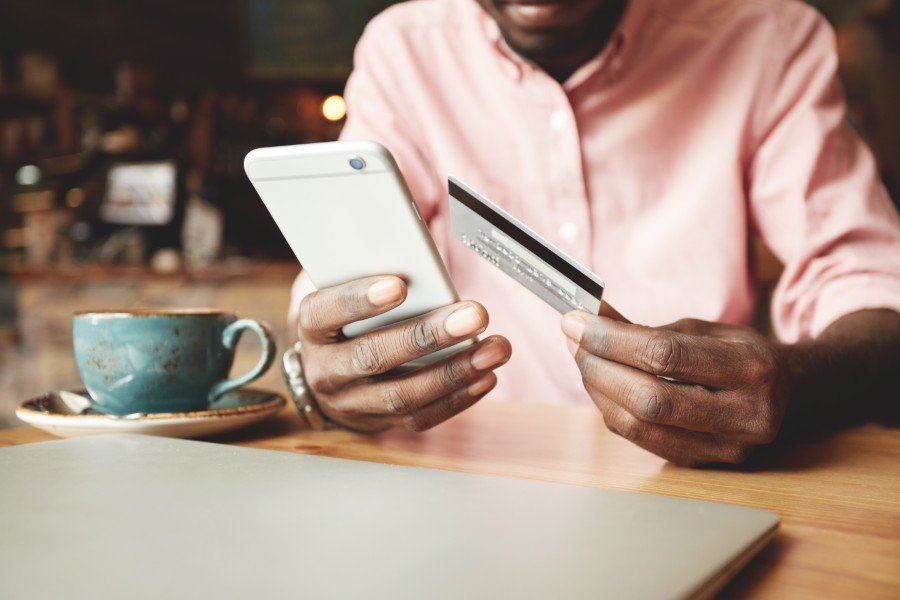switching-credit-cards-man-with-phone-and-credit-card-coffee-shop