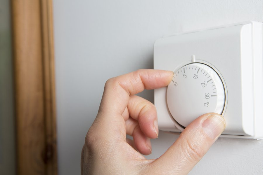 Close Up Of Female Hand On Central Heating Thermostat